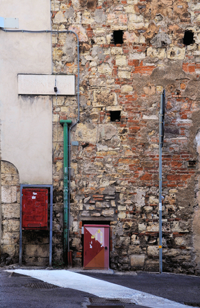 Remains of medieval wall with street name and old postal service box. Stock Photo
