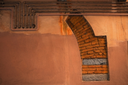 Fragment of medieval arch in building facade with a group of pipes for gas.