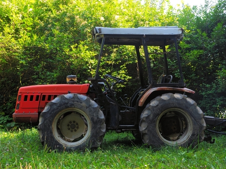Red tractor for transporting logs cut in the natural environment. Stock Photo