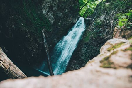 In a mountain forest, a waterfall in a gorge
