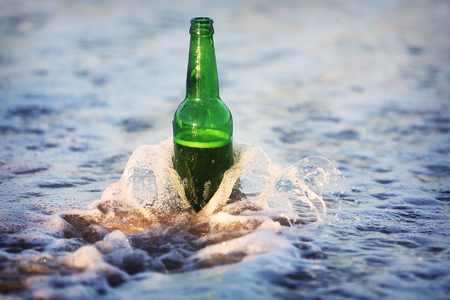 A bottle of beer on the beach. Waves wash a beer bottle. Stock Photo