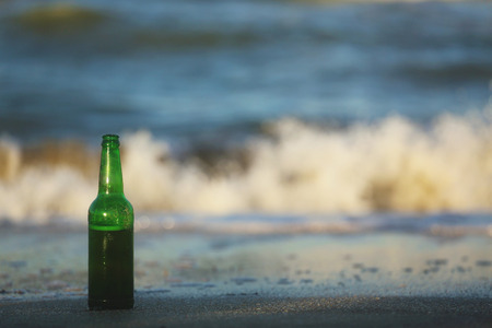 green beer bottle: Green beer bottle sitting in the sand on the seashore. Stock Photo
