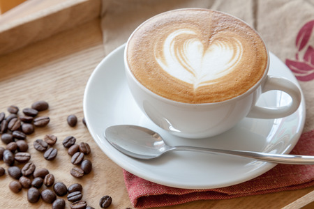 acidity: A cup of latte and coffee beans Stock Photo