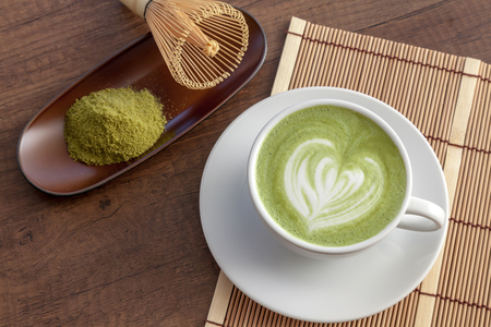 Matcha latte art heart shape on top on wooden table with some green tea powder beside, Japanese style