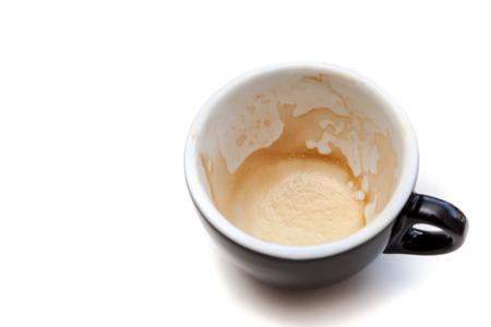 Fleck Kaffee in schwarzer Tasse auf weißem Hintergrund