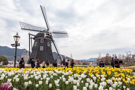 NAGASAKI, JAPAN - MARCH 18, 2017 :The windmill  at Huis Ten Bosch theme park with many color tulips garden in Sasebo, Nagasaki, Japan.