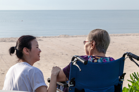 Mother and daughter sit together in front of the beach looking at each other.  This shows the happiness and love in family. This can be related with any article about family, elder, health. 版權商用圖片