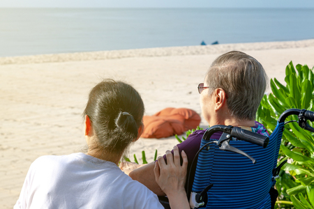 Mother and daughter sit together in front of the beach looking at the sea.  This shows the happiness and love in family. This can be related with any article about family, elder, health. Banque d'images - 126628456