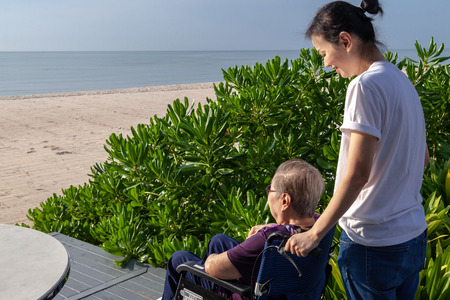 Daughter push the wheel-chair forward for her mother in front of the beach.  This shows the warmth relationship in family. This can be related with any article about family, elder, health.