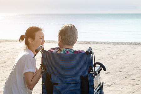 Mother and daughter sit together in front of the beach looking at each other.  This shows the happiness and love in family. This can be related with any article about family, elder, health. Banque d'images - 126628460