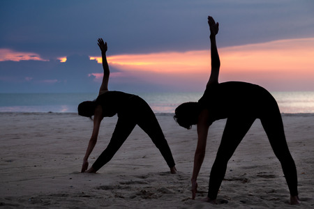 practise yoga, Triangle pose at the beach in early morning.