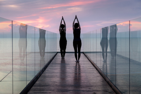 Two people practise yoga, Tree pose at the hotel in early morning. Banque d'images - 126628475