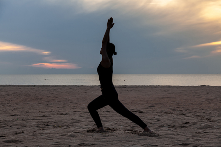 practise yoga, Warrior pose on the beach in early morning Banque d'images - 126628489