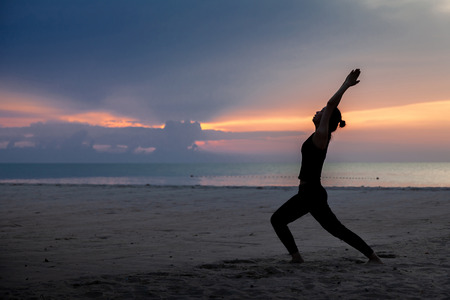 practise yoga, Warrior pose on the beach in early morning. Banque d'images - 126628490