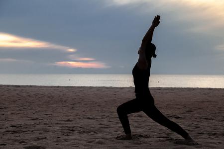 practise yoga, Warrior pose on the beach in early morning 版權商用圖片