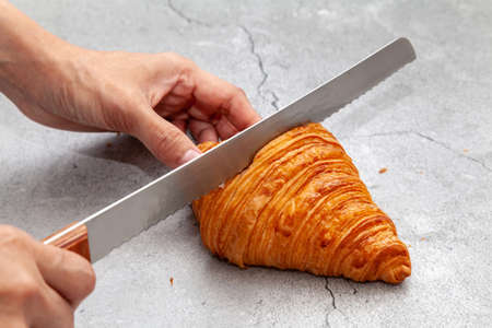 Sliced fresh baked croissant with bread knife on cement background. 版權商用圖片