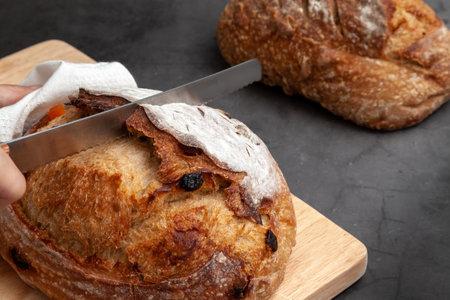 Baker slice sourdough bread with bread knife on dark cement background. 版權商用圖片 - 162150492