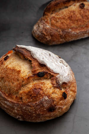 Sourdough bread with mixed fruits and nuts on dark cement background.