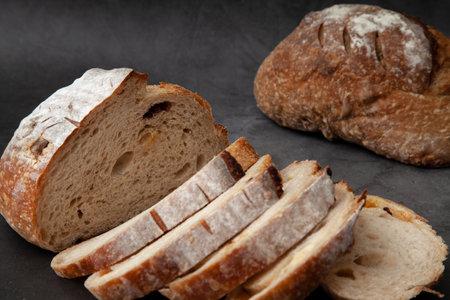 Sliced sourdough bread on dark cement background.