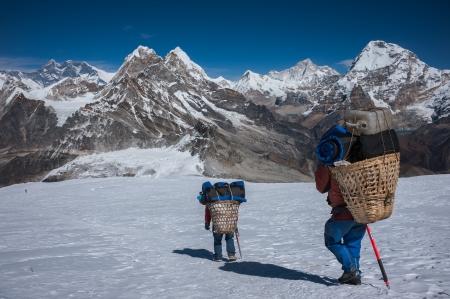 loads: Nepali porters carrying heavy loads in Himalayas Stock Photo
