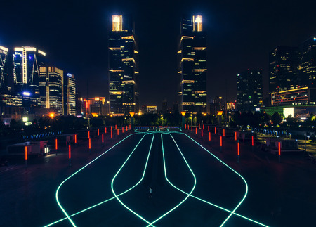 Zhengzhou East Railway Station West Square huge beautiful square light strip pattern and Zhengdong New District new landmark green land twin towers night view Editorial