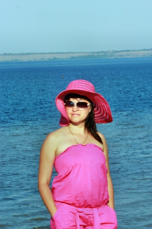 Girl in a hat and sunglasses on the background of the sea Stock Photo