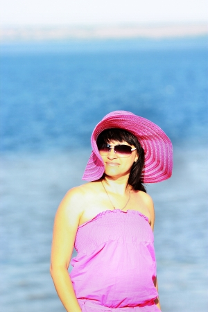 A girl in a pink dress on a background of water