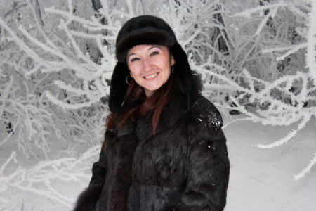 Beautiful girl stands near the snow-covered tree Stock Photo