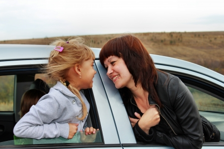 Smiling mother and daughter looking at each other, looking out of car photo