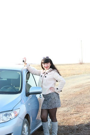 Happy brunette in front of his car with the keys in hand photo