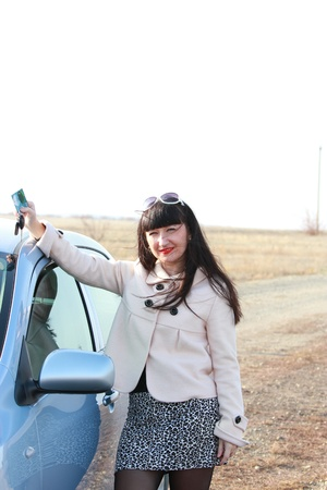 A young girl near a car with a bank card and keys in hand photo