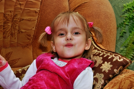 The little four year old girl is resting on the couch Stock Photo - 15905586