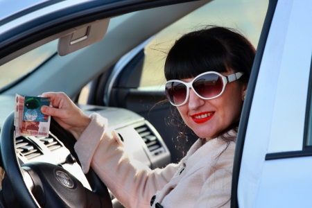 A woman wearing sunglasses in a car with a credit card and cash in hand photo