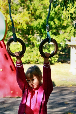 Blonde girl hanging on the rings photo
