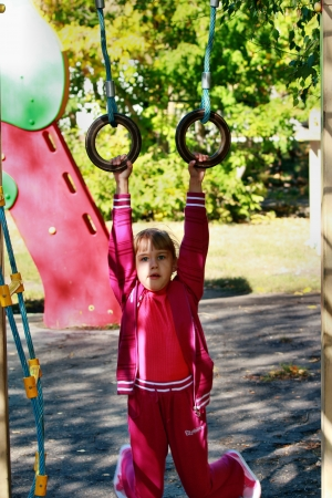 The girl in a sports suit hanging on rings photo
