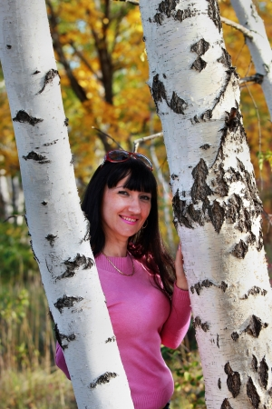 Happy brunette in a forest about two birches photo