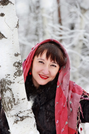A smiling girl in a pink scarf, stands near the birch trees in winter forest Stock Photo