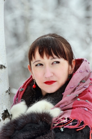 Portrait of an attractive woman in the winter forest