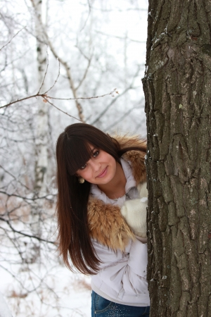 Pretty smiling girl near a tree in a winter forest Stock Photo