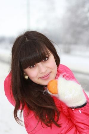 Beautiful girl mandarin in hand in the winter woods Stock Photo