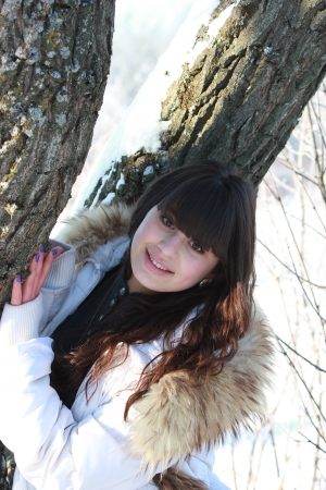 A girl in a white jacket, standing near a tree