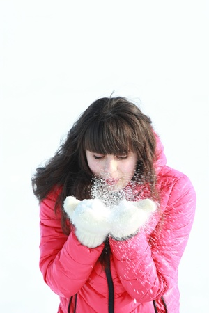 A girl in a pink jacket blows away the snow mittens