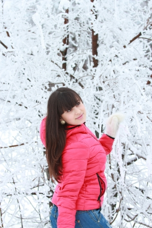 Young brunette in a pink jacket in the winter woods near a snow-covered tree Stock Photo