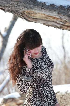 Girl in leopard dress talking on the phone Stock Photo
