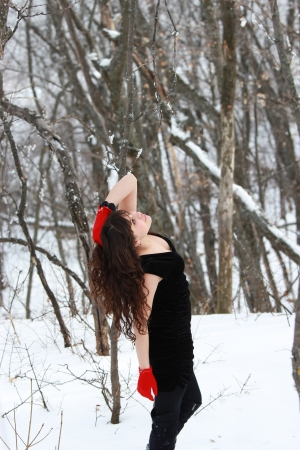 A girl stands in a black dress and red gloves raised his head and hand up