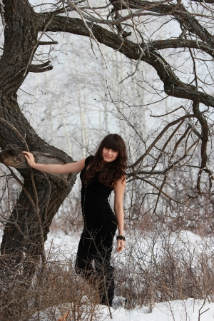 Attractive girl in winter forest near a tree Stock Photo