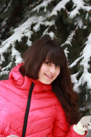Beautiful girl in winter snow covered fir near Stock Photo