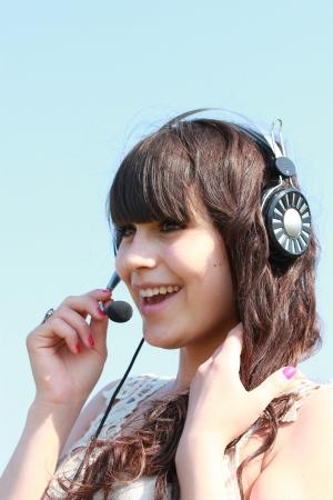 Happy brunette in headphones with microphone Stock Photo