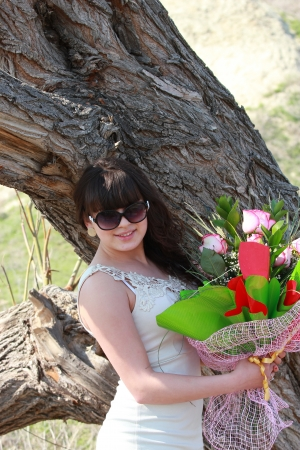 A young girl with a bouquet of roses beside an old oak Stock Photo