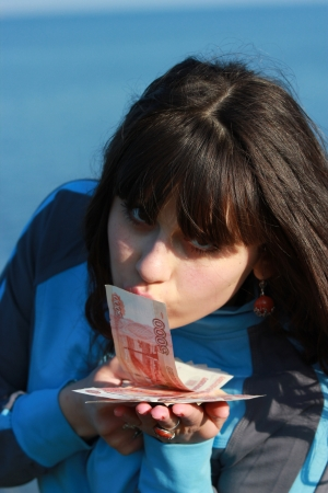 thousandth: The girl kisses the five thousandth bills Stock Photo